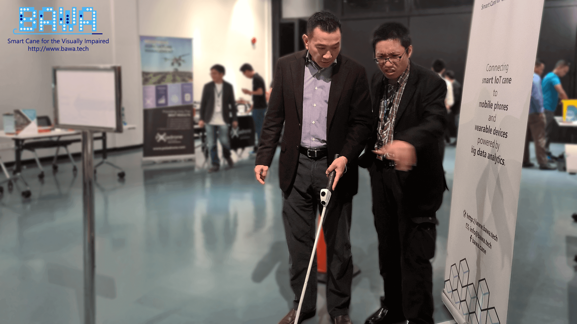 Dato Loh Yuen Tuck from The IoT Solutions Sdn Bhd listens on while Daniel Vong is explaining how to use a white cane.